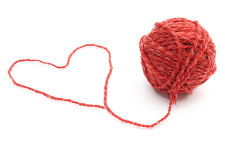 Closeup of heart shape of red wool and wool ball on white background photo