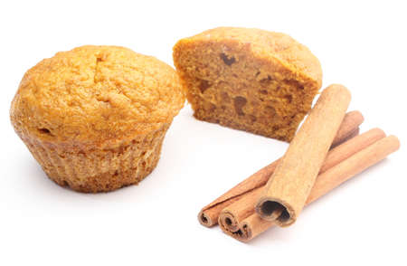 Closeup of fresh baked carrot muffin and stack of cinnamon sticks  Isolated on white background photo