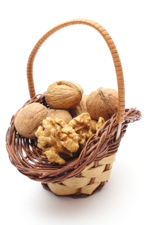 Closeup of walnut without shell and stack of walnuts in wicker basket  Isolated on white background photo