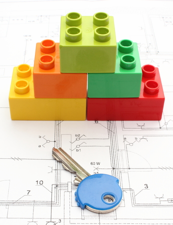 Colorful building blocks and key lying on construction drawing of house photo