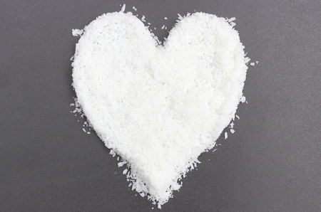desiccated: Closeup of heart of white desiccated coconut isolated on black background