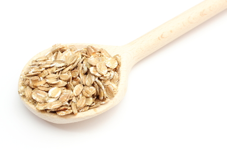 Heap of rye flakes on wooden spoon  Isolated on white background photo