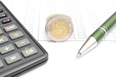 Closeup of coins, pen and calculator lying on spreadsheet, financial document with numbers photo