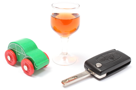 Closeup of glass of wine with car key and old wooden toy car, key car and alcohol, don photo