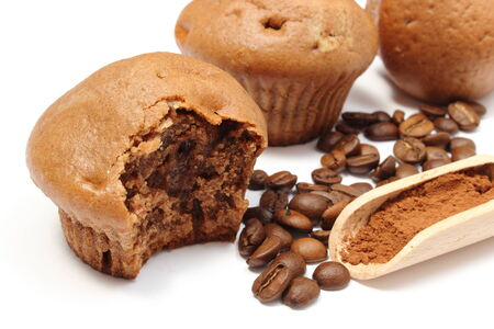 Closeup of fresh baked coffee muffins, coffee grains and powdery cinnamon on wooden spoon, bitten muffin  Isolated on white bakcground photo