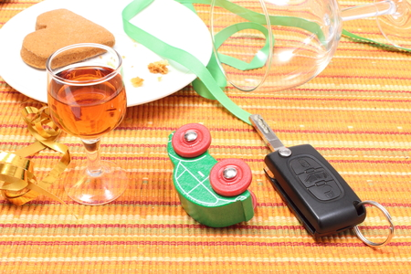 irresponsible: Closeup of car key and overturned model vehicle with glass of wine lying on table after party, car key and alcohol, don