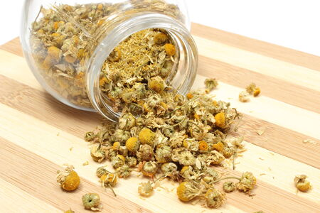 Closeup of dried chamomile, dried chamomile pouring out of glass jar on wooden cutting board photo