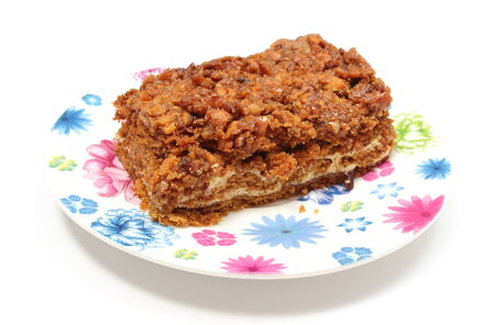 walnut cake: Piece of fresh, delicious walnut cake lying on colorful plate  Isolated