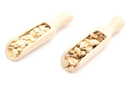 Heap of oatmeal and rye flakes on wooden spoon  Isolated on white background photo