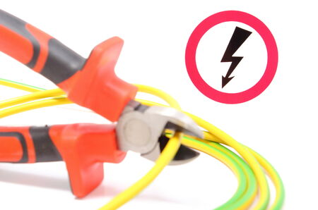 disconnecting: Metal pliers with green-yellow electric cable and high voltage danger sign in background, pliers cut the cable  Isolated on white background Stock Photo