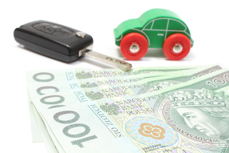 Heap of money, old wooden green toy car and key car  Isolated on white background photo