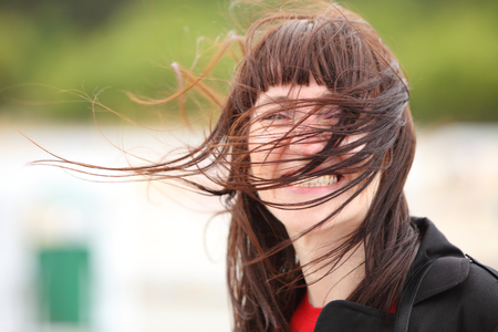 Woman at the seaside, on the beach on a windy day Stock Photo