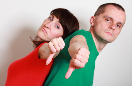 pessimist: Unhappy and angry woman and man showing thumbs down, disapproval offer or situation, negative emotions