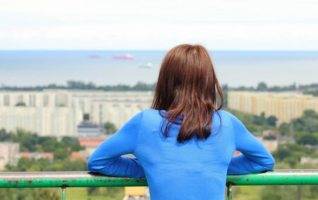 Woman watching view of the city Gdansk from observation tower, woman looks at panorama of city, style melancholy concept  Stock Photo