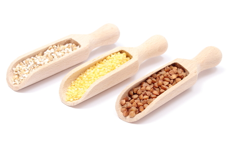 Closeup of buckwheat, millet groats and barley groats on wooden spoon, healthy food and healthy nutrition  Isolated on white background photo