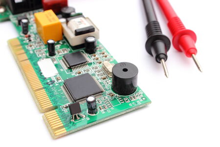 microelectronics: Closeup of cable multimeter and circuit board isolated on white background
