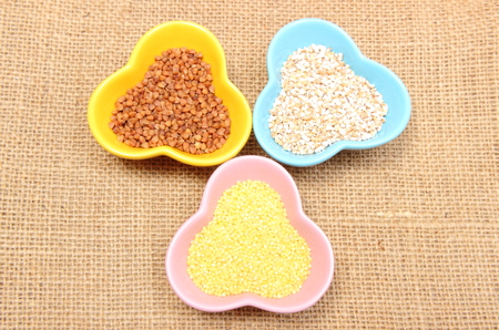 Closeup of buckwheat groats, barley groats and millet groats in colorful bowl lying on jute canvas, healthy food and healthy nutrition photo