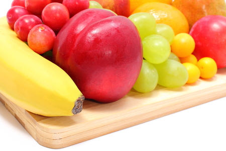 Fresh ripe fruits lying on wooden cutting board, desk of fruits, concept for healthy eating  Isolated on white background photo