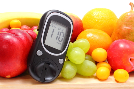 Glucose meter and fresh ripe fruits lying on wooden cutting board, concept for healthy eating and diabetes  Isolated on white background photo