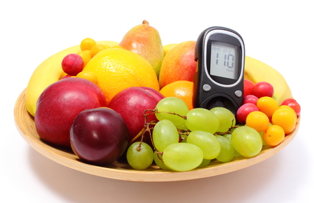 Fresh ripe fruits and glucose meter lying on wooden plate, concept for healthy eating and diabetes  Isolated on white background photo