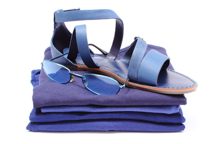 Leather sandals of woman and sunglasses lying on pile of blue shirts and clothes, accessories for holiday  isolated on white background photo