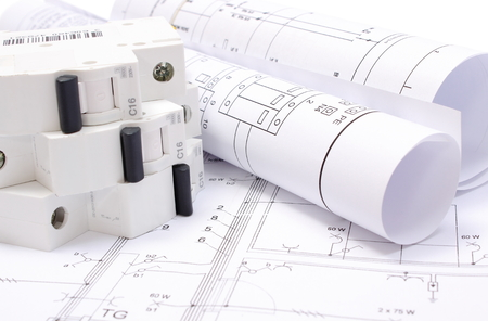 Rolled electrical diagrams and electric fuse lying on construction drawing of house, drawings for the projects engineer jobs