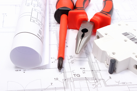 Rolled electrical diagrams, electric fuse and work tools lying on construction drawing of house, drawings for the projects engineer jobs Stock Photo