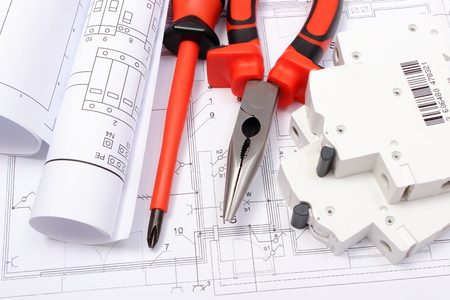 Rolled electrical diagrams, electric fuse and work tools lying on construction drawing of house, drawings for the projects engineer jobs 版權商用圖片