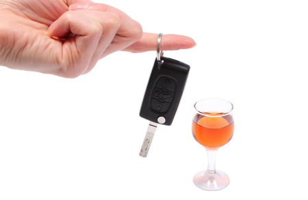 Hand of woman with key car and glass of wine, don photo