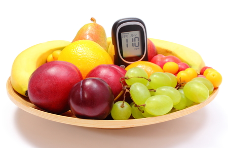 Fresh ripe fruits and glucose meter lying on wooden plate, concept for healthy eating and diabetes. Isolated on white background photo