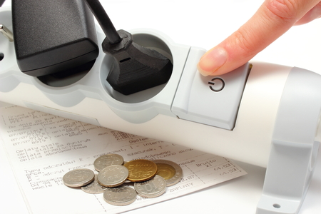Finger of woman turns off electrical extension, electrical plugs connected to electrical power strip, electricity bill with coins, concept for energy saving photo