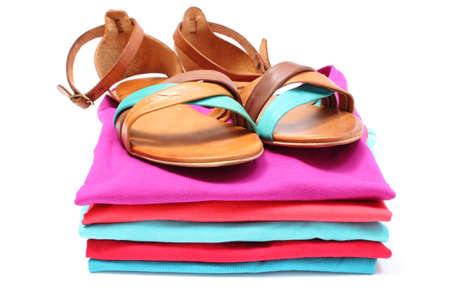 pile of clothes: Leather sandals lying on pile of colorful shirts. Isolated on white  Stock Photo