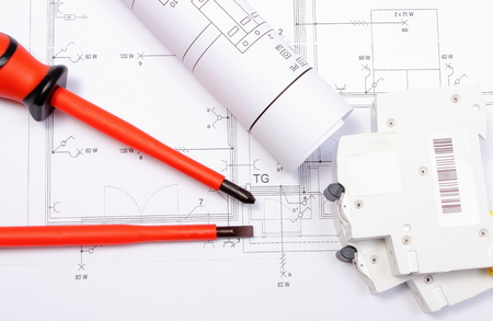 Rolled electrical diagrams, electric fuse and red screwdrivers lying on construction drawing of house, drawings for the projects engineer jobs