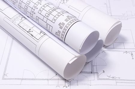 Rolled electrical diagrams lying on construction drawing of house, drawings for the projects engineer jobs Stok Fotoğraf