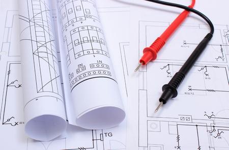 ingeniero electrico: Rollos de esquemas eléctricos y cables de multímetro que mienten en el dibujo de la construcción de las casas, dibujos y herramientas para los trabajos del ingeniero