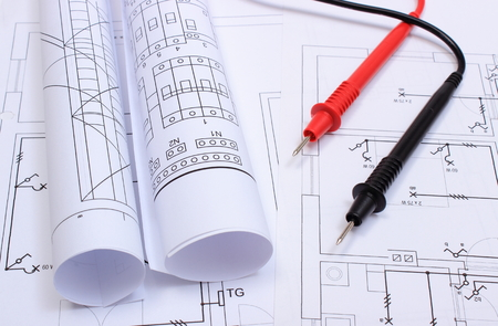 Rolls of electrical diagrams and cables of multimeter lying on construction drawing of house, drawings and tools for engineer jobs Standard-Bild