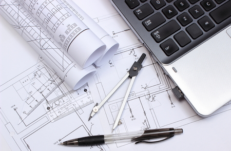 Rolls of electrical diagrams, construction drawings of house, accessories for drawing and laptop, drawings and accessories for the projects engineer jobs Standard-Bild