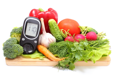 Glucose meter and fresh ripe raw vegetables lying on wooden cutting board, desk of healthy organic vegetables, concept for healthy eating and diabetes. Isolated on white background