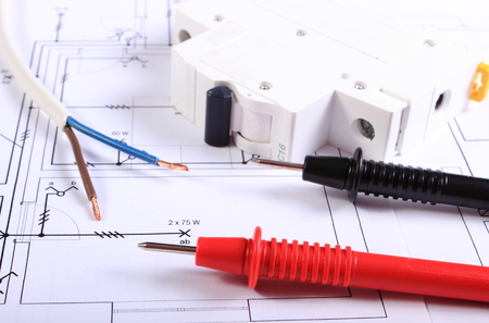 electrical engineering: Cables of multimeter, electric wire and electric fuse on construction drawing, electrical drawings and tools for engineer jobs