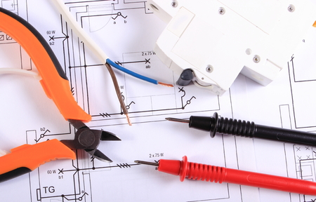 Cables of multimeter, metal pliers, electric wire and fuse on construction drawings, electrical drawings and tools for engineer jobs
