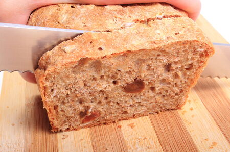 Hand of woman with knife slicing fresh baked wholemeal bread photo