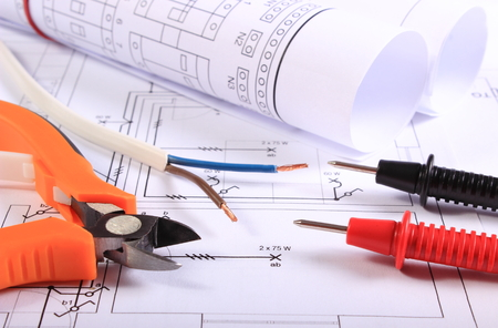 Cables of multimeter, metal pliers, electric wire and construction drawings, electrical drawings and tools for engineer jobs