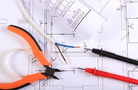Engineers: Cables of multimeter, metal pliers, electric wire and construction drawings, electrical drawings and tools for engineer jobs