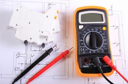 ingeniero electrico: Multímetro con los cables y fusibles eléctricos que mienten en el dibujo de la construcción de casas, planos eléctricos y herramientas para los trabajos del ingeniero Foto de archivo
