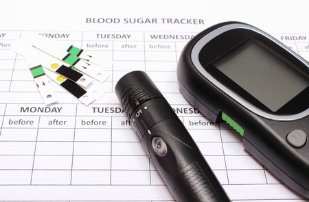 medical device: Glucometer, lancet device and strip for glucose test lying on empty medical forms for measurement sugar in blood, concept for measuring sugar level Stock Photo