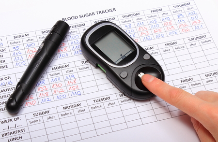 Woman doing test for determination level sugar, medical form with results of measurement of sugar, concept for diabetes photo