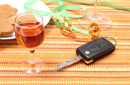 after the party: Closeup of car key with glass of wine lying on table after party, car key and alcohol, don Stock Photo