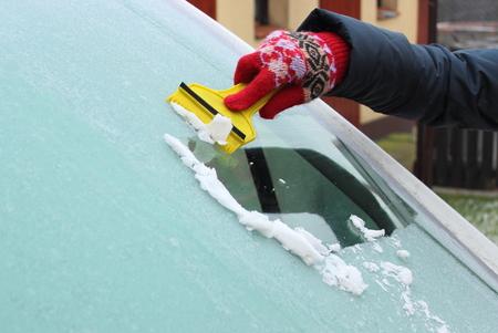 車のフロント ガラスからの雪と氷をこする手袋の女の手