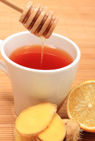 Cup of healthy tea with honey ginger and lemon on wooden background, concept for healthy nutrition photo