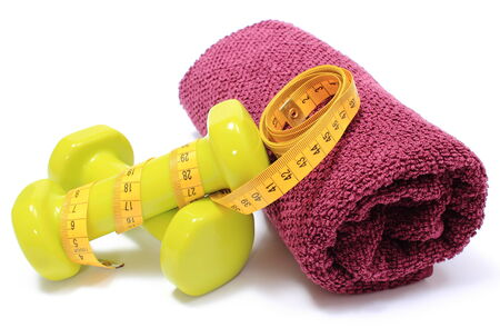 Green dumbbells and purple fluffy towel for using in fitness and measure tape, concept for slimming and healthy lifestyle photo
